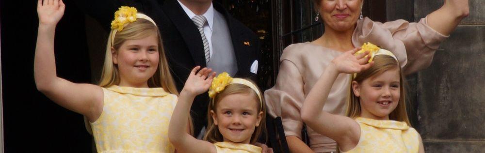 A royal family waving from the palace's balcony