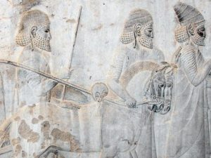 A bas relief. A procession of men walk next to twosmall  horses. The horse's head are at the same level than the men's shoulders.