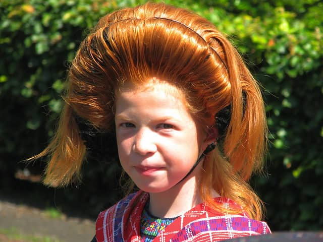 A girl with the crisscross over her shoulders. Her hair is up in a traditional hairdo: It goes up for about 10 cm, and then curves back.