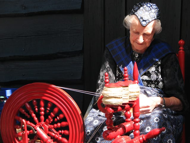 A woman spinning outdoors. She wears a traditional dress that is mostly black and blue. A cloth covers hers shoulders and crisscrossed over her chest.
