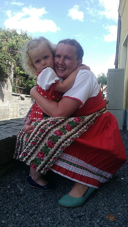 A woman embraces a child. Both wear traditional red dresses with white shirts underneath