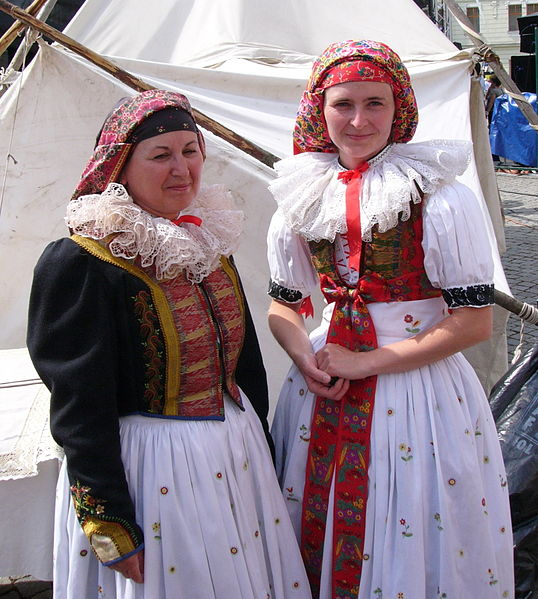 Two women. Both wear big ruffled white collars and a red cloth that covers all their hair. Both their skirts are white with patterns. The woman on the left wears a black vest with red and yellow decorations. The other woman wears a red vest.