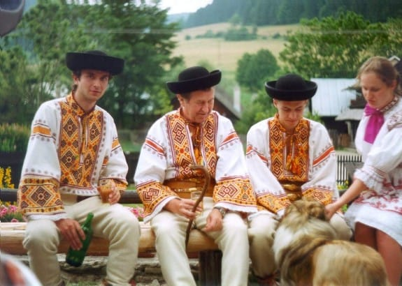 Three men sitting. They were white shirts with golden-red stripes on the front and on the end of the sleeves. They wear black hats, wide belts, and beige pants