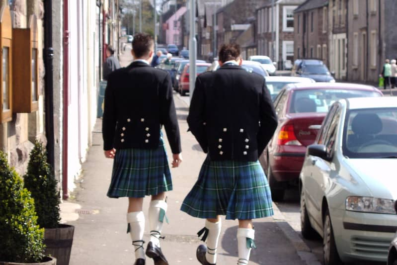 Two men walking on a sidewalk, their backs to the camera. They wear green kilts, white socks, and black shoes. The top of their attire is a black jacket.