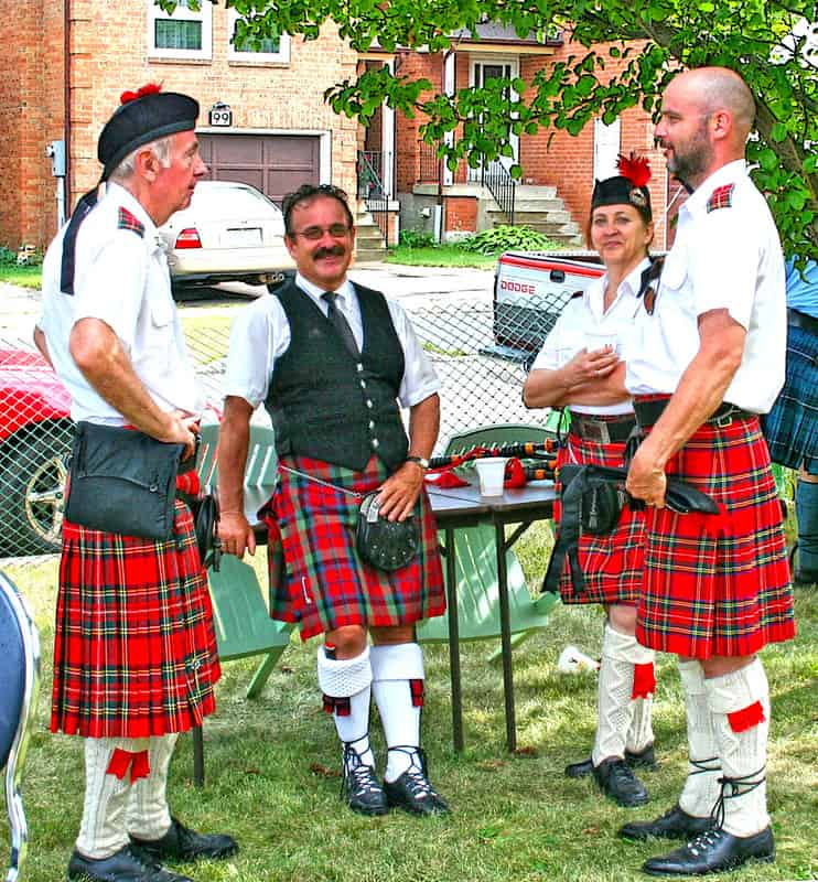Three men and a woman. they all wear white shirts, red kilts, white socks and black shoes.