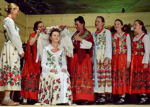 One woman sits on a stage while other women surround her and dress her. They are wearing red or white dresses. All the dresses have embroideries.