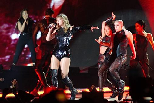 Taylor singing on stage, accompanied by backup dancers.