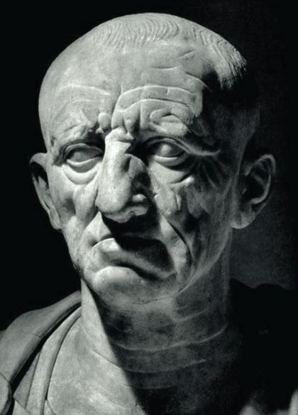 Black and white photo of a statue. It is a marble bust of a an older man.