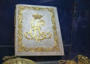 A book with a beautifully decorated cover is displayed in a museum.