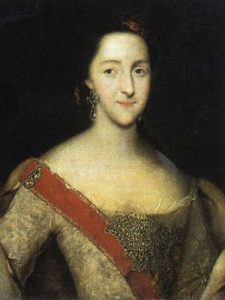 Portrait of a young woman with black hair. She has a long face and wears a beige delicate dress and a red sash.