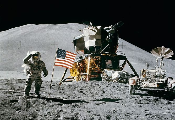 Picture taken on the lunar surface. It shows Apollo 15's astronaut Jim Irwin saluting the American flag that stands next to him. In the background are the spacecraft and a mountain.
