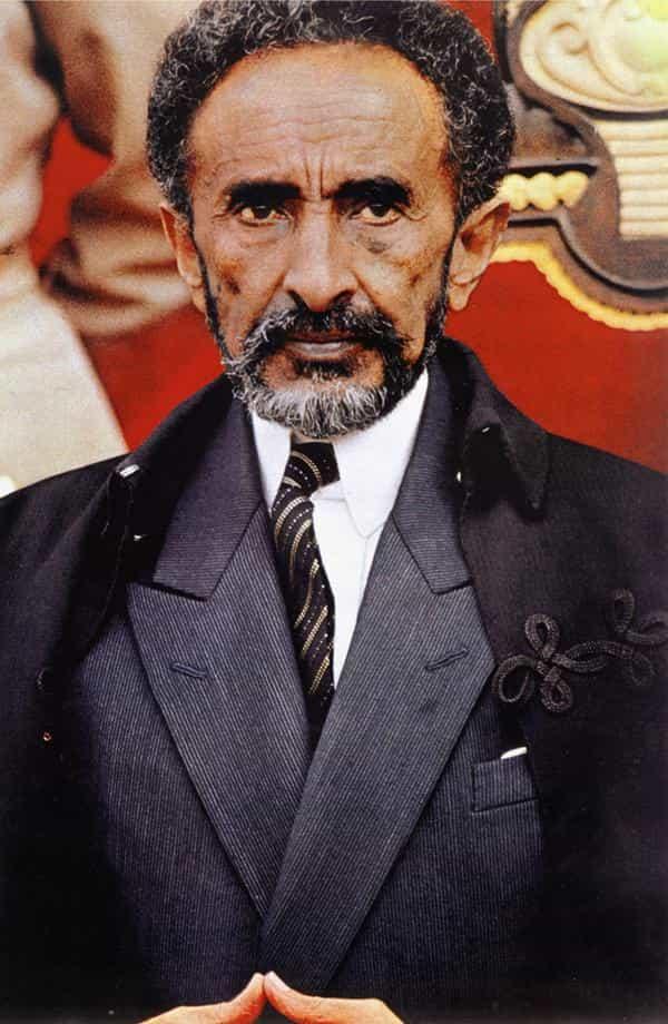 Bearded man in his fifties or sixties, dressed in elegant gray suit. He wears a black coat.