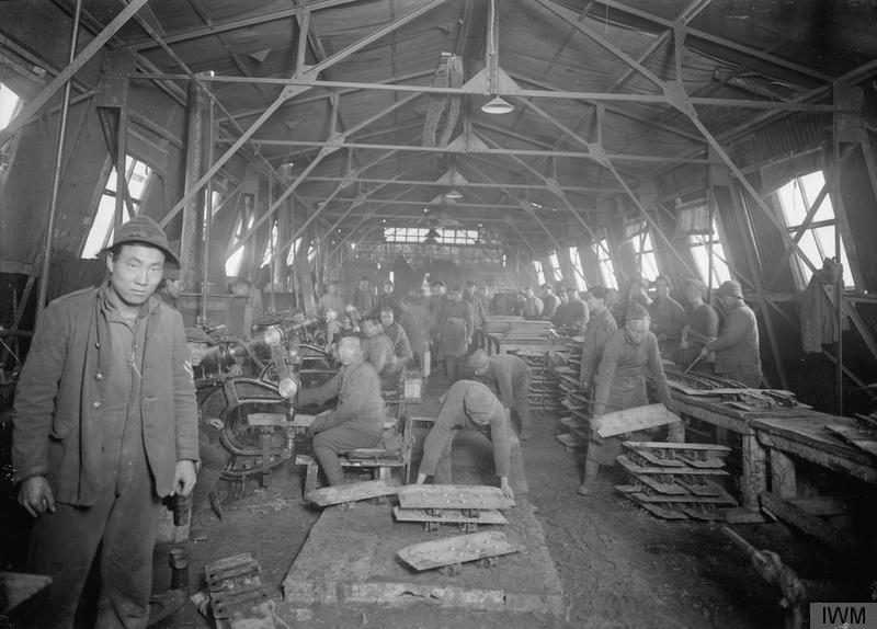Black and white picture inside a warehouse. It is filled with Chinese workers.