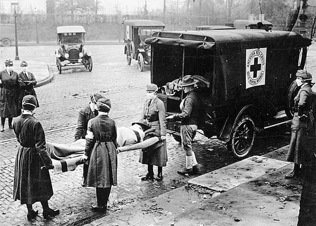 Outdoors, the street. Four nurses wearing masks carry a stretcher with a body. They are taking it to an ambulance with the Red Cross sign. Three other nurses and the driver look on.