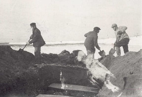 Three men digging a large grave. inside the grave are some coffins.