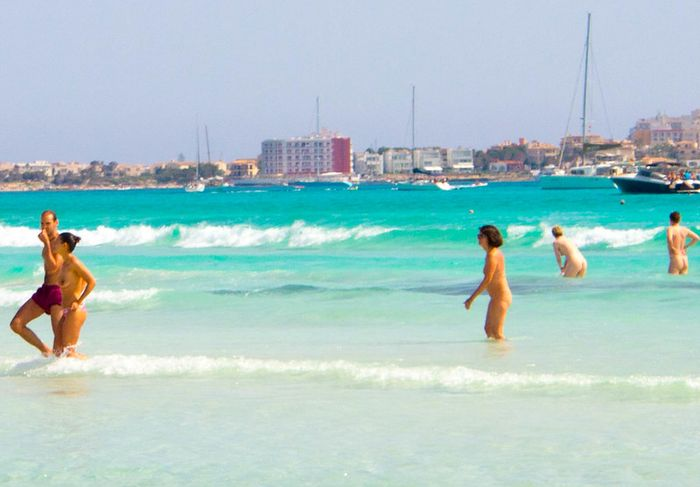 Picture of a sunny nudist beach. Five people are swimming in a turquoise, calm sea, and four of them are naked.
