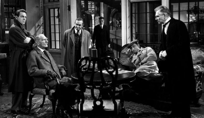 Black and white picture. Six men stand or sit in a living room discussing something.
