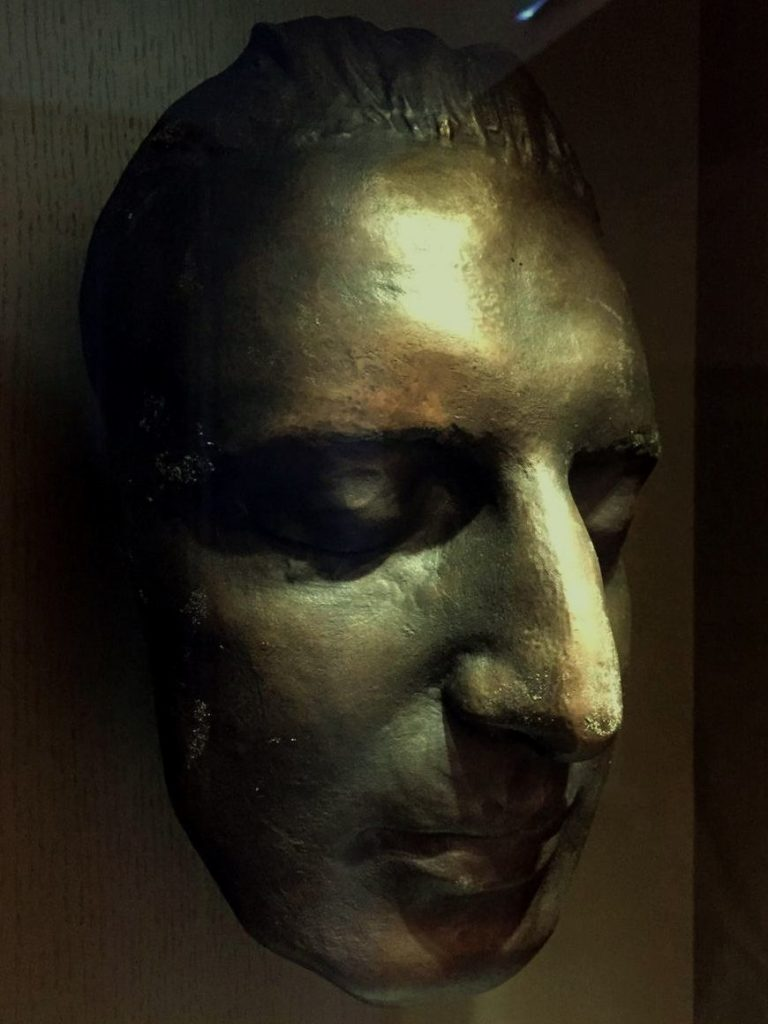 Probably Mozart's death mask. He has a long, thin, serene face. His nose is prominent and curved, his lips are medium-sized.