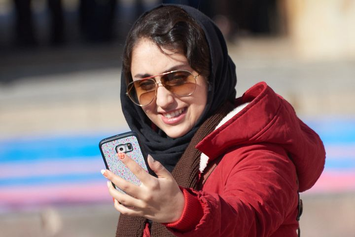 A woman dressed in red and black and wearing sunglasses takes a selfie wit her phone.