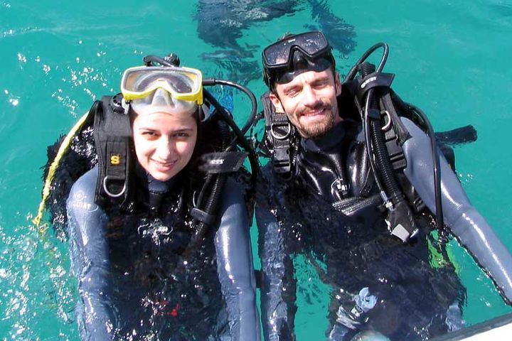 Two scuba divers, a man and a woman, emerge from the sea.