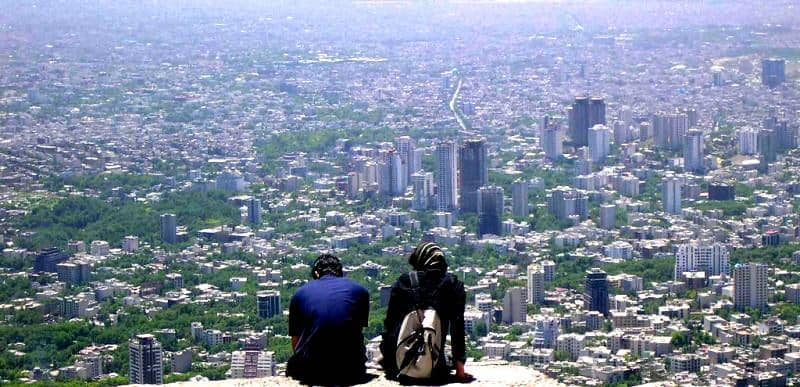 A panoramic view of Tehran from a mountain. In the foreground a couple, sitting on top of the mountain, take in the view of the city.