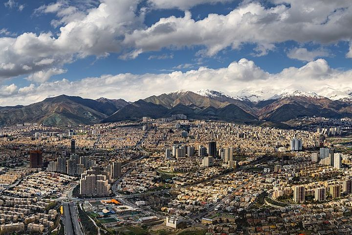 An aerial view of a large modern city with many buildings and highways. It is in a valley, next to a chain of mountains.