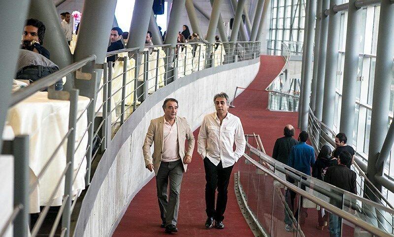 Inside a modern glass-building. Two men walk on a ramp.