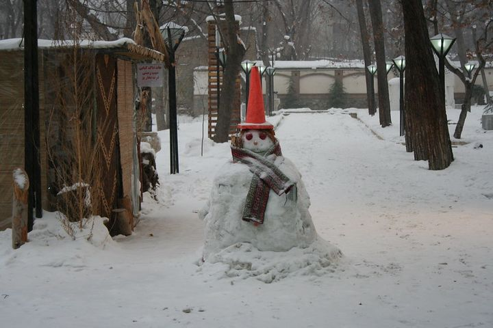 A snowman in the middle of a street covered in snow.