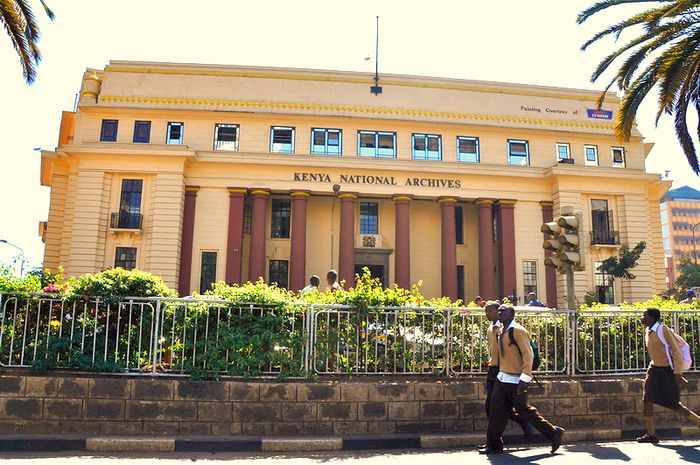 Big yellow European building with magenta columns. It is the Kenya National Archives.