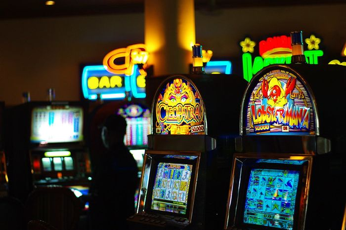 Inside a casino. Picture of several machines and electronic games.