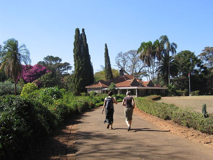 Two women walk on a road towards the same house. The house seats on large grounds. There is only nature around.