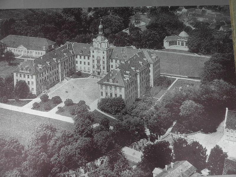 Black and white photo of a u-shaped, 3-storey high palace.