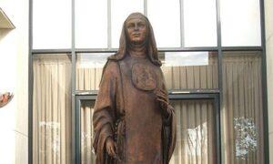 Bronze statue of a standing nun.