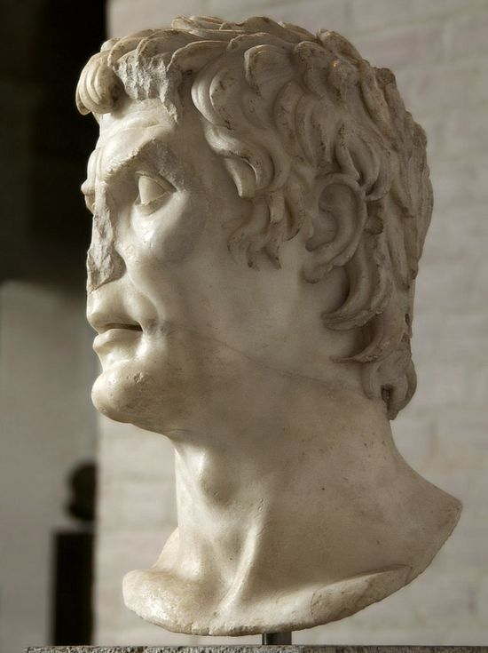 Same marble statue seen in profile. His straight forehead slants backwards slightly. He has a prominent brow ridge. His rounded chin juts forward, he has a prominent Adam's apple and medium-sized ears.