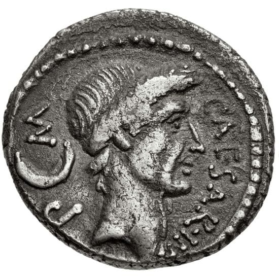 "A silver coin with a man's face on it. The man wears a laurel wreath. He has an elegant a bit long face. is nose is long, his chin is round, his neck is thin. The coin reads ""Caesar."""