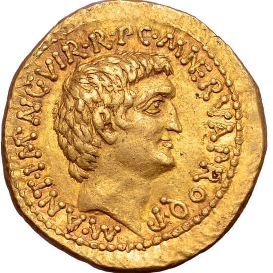 A golden coin with a man's face on it. He has choppy, abundant hair that covers the top of his forehead. His forehead is short, he has a powerful, aquiline nose that does not protrude much but sharply angles downward, his chin is strong and juts forward.