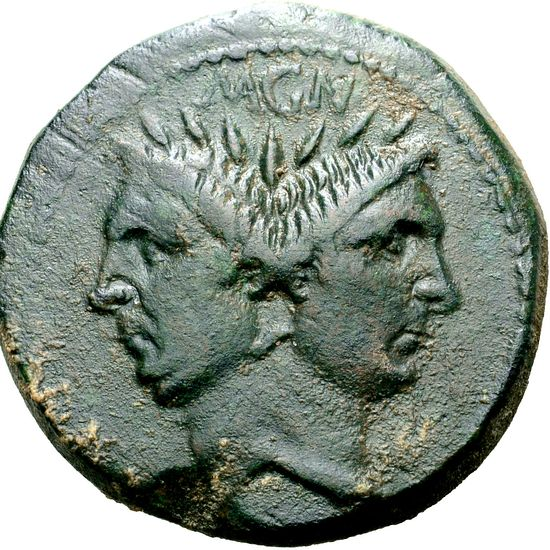A different type of coin, in a different material too. The coin has two faces on it. They look in opposite direction, one to the left, the other to the right. They are joined by the backs of their heads. Both men have Pompey's features.