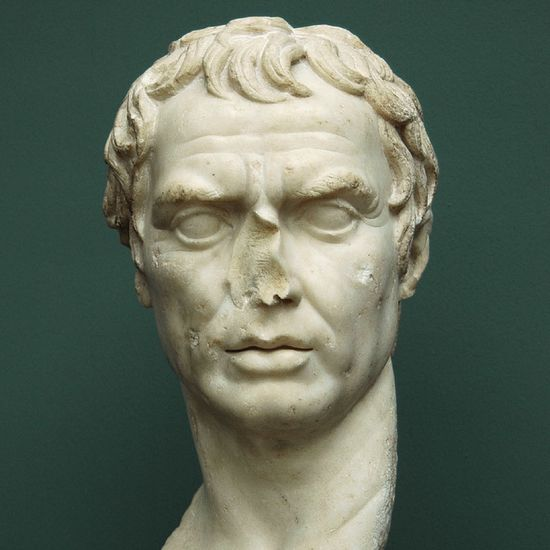 A handsome male face in white marble. It has longish, wild hair that covers part of his forehead. Squarish face, fleshy lips, pronounced eyebrows, a strong jaw, big eyes, and wrinkles in the forehead. Pictured from the front.