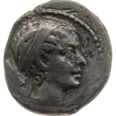 A silver coin with the face of a very beautiful woman. The craftsmanship of this coin is great. Every detail of her face is visible. She has her hair pulled back and wears a diadem. Her forehead is medium-sized and straight, her nose is aquiline. She has full lips and a strong, defined chin.