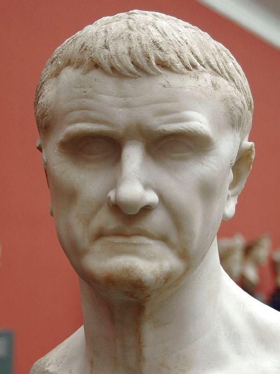 Marble head showing the same man of the previous illustration. His face is triangular, the ample forehead being browder than his squared jaw. He looks dignified and distant. His face has sharp line, he has wrinkles on his forehead, deep-set eyes, a strong nose, a tight mouth, high cheekbones.