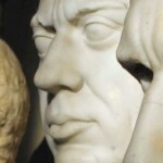Two marble faces of men in the foreground. There is another statue in the background.