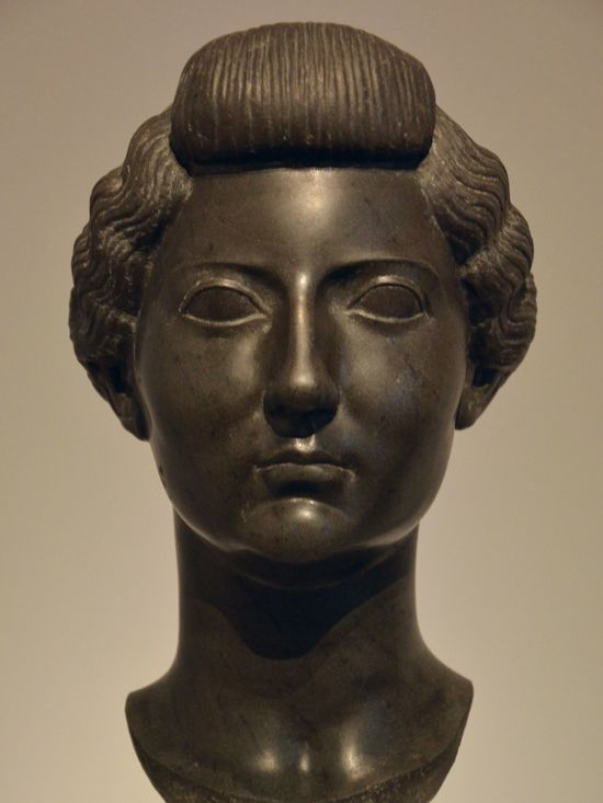 Same statue as before, front. She has an elaborate hairdo. Her forehead is high. Her face is a mix between square and oval. Her nose is thin and long, her mouth is small and pouty, her cheekbones are fleshy, her eyes are medium-sized and cat-like. She looks proud.
