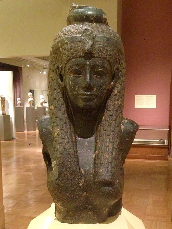 Another Egyptian bust. The woman again wears the same headdress. Her face is a little kinder and looks a bit less generic. Her face is oval, she has a medium-sized mouth, a thin, long nose.