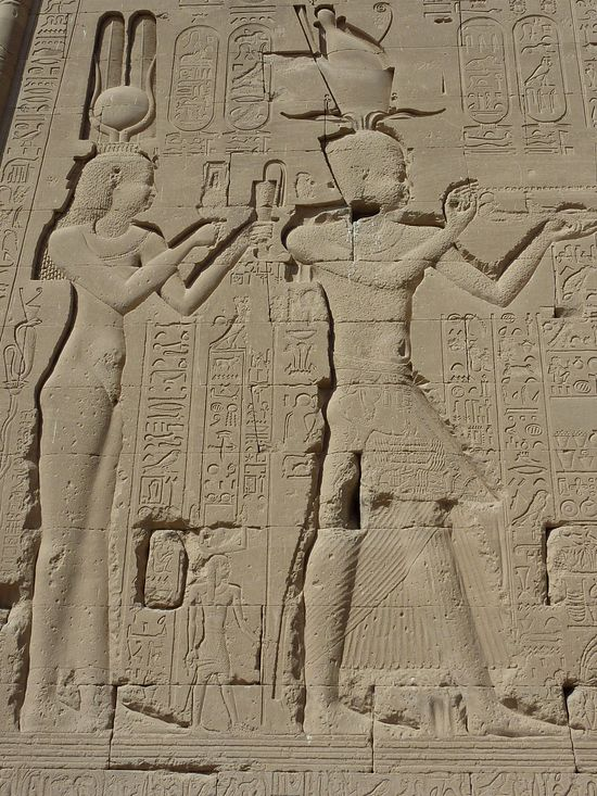 Egyptian stone relief. Two people seen from the profile. The woman wears a dress and a crown and the man wears an Egyptian skirt and headdress. They are both standing and have their arms lifted in adoration.