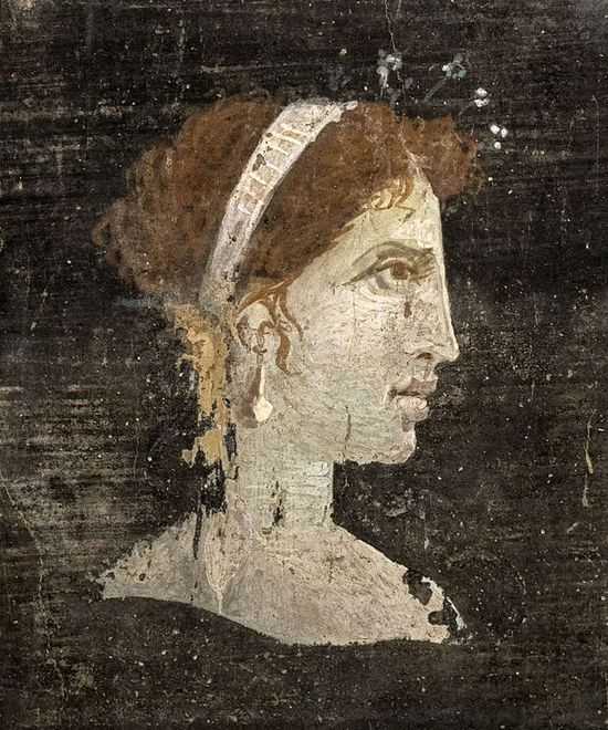 Painting of a woman seen in profile. The background is black. The woman has reddish hair pulled back in a chignon. She wears a band on her head and a pearl earring. She has a straight, high, slanting forehead, curved eyebrows, a long nose, thick lips, and a rounded chin. Her eyes are brown and her skin is pale.