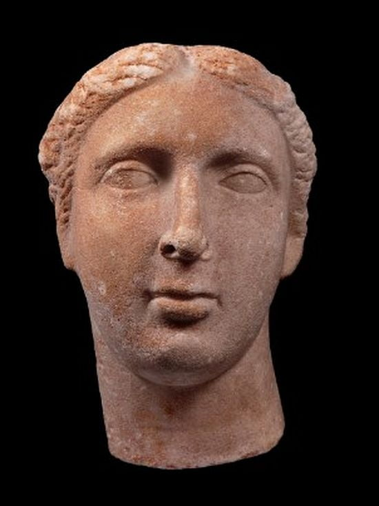 Stone head of a woman. She has an oval face, hair parted in two, small forehead, deep-set, wide-set eyes, long, thin nose, medium-sized mouth, rounded chin.