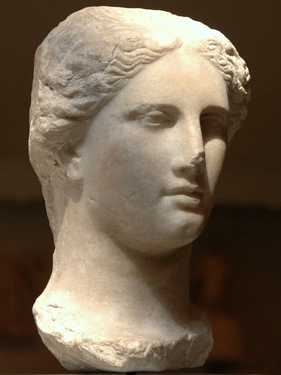 Marble head of a woman. Very idealized. Her hair parts in the middle. Her eyes are small and deep-set. Her nose is straight, her mouth small with medium-sized lips, her chin is strong and round.