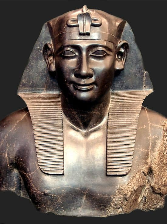 Basalt bust of a man. It is in the Egyptian style. The man wears the pharaoh's headdress and his torso is nude.