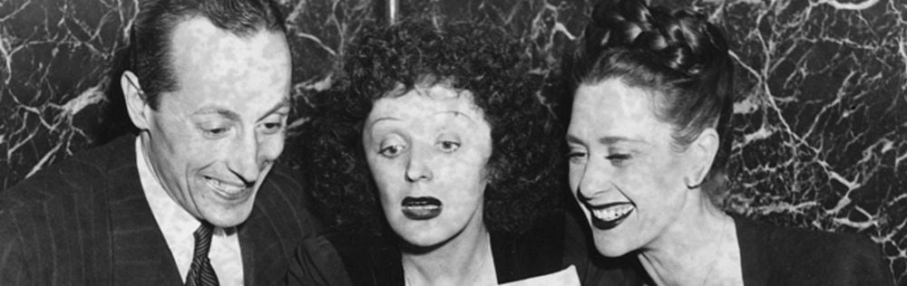 White and black photo of Edith Piaf and two friends reading a newspaper.