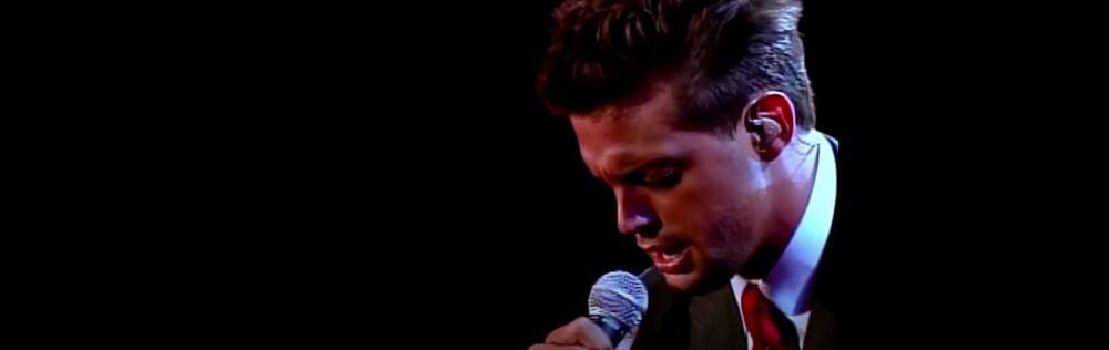 Luis Miguel singing on stage.